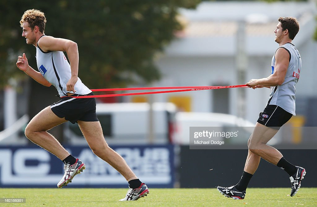 Jarrod Witts runs with a rubber band around him held by Jordan Russell during a Collingwood Magpies AFL training session at Gosch's Paddock on February 20, 2013 in Melbourne, Australia.