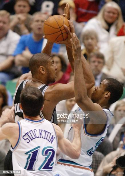 Jarron Collins of the Utah Jazz catches the elbow of Tim Duncan of the San Antonio Spurs before Jazz player John Stockton during the first quarter 17...