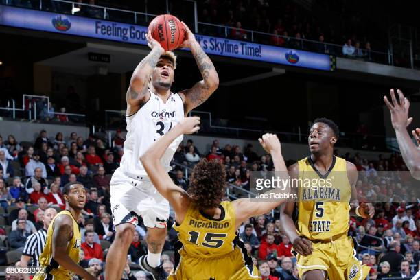 Jarron Cumberland of the Cincinnati Bearcats drives to the basket against Fausto Pichardo and Tobi Ewuosho of the Alabama State Hornets in the first...