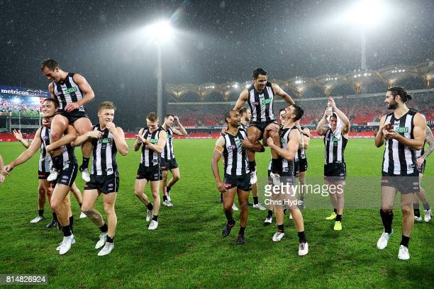 Jarryd Blair and Daniel Wells of the Magpies are chaired from the field after their 150th and 250th match during the round 17 AFL match between the...