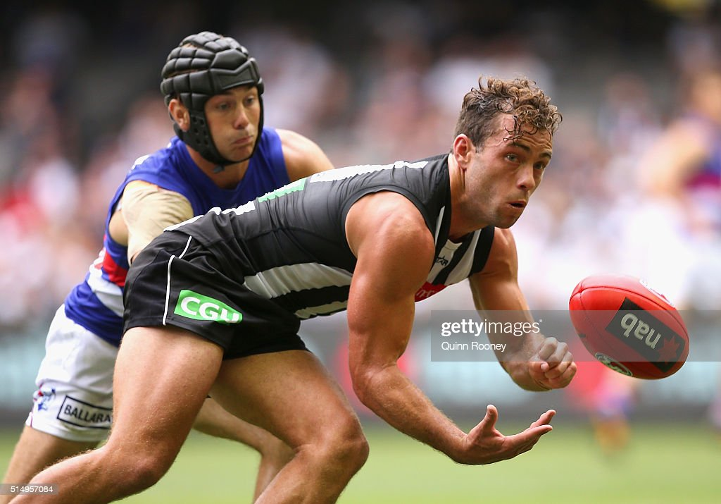 Jarryd Blair of the Magpies handballs whilst being tackled by Caleb Daniel of the Bulldogs during the 2016 NAB Challenge AFL match between the Collingwood Magpies and the Western Bulldogs at Etihad Stadium on March 12, 2016 in Melbourne, Australia.