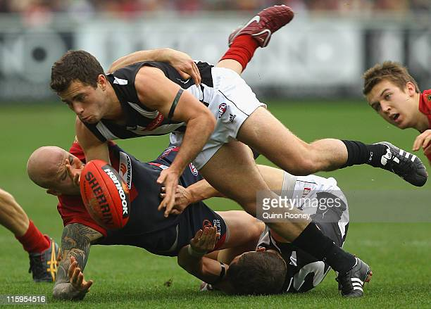 Jarryd Blair of the Magpies handballs whilst being tackled by Nathan Jones of the Demons during the round 12 AFL match between the Melbourne Demons...