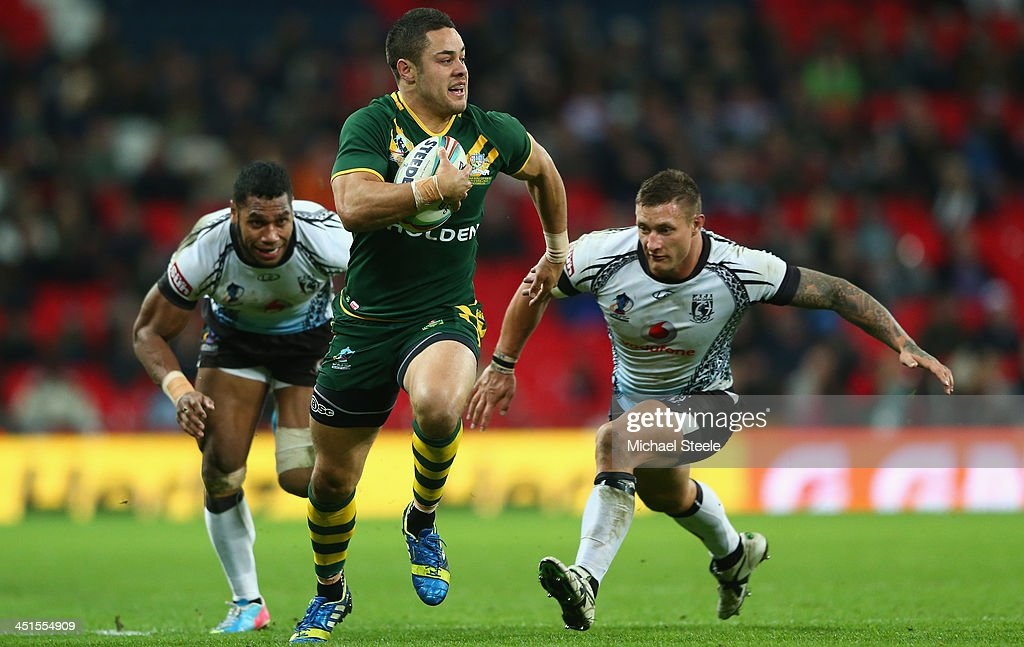 Jarryd Hayne (C) of Australia bursts past Sisa Ledua Waqa (L) and Tariq Sims (R) of Fiji on his way to scoring a try during the Rugby League World Cup Semi Final match between Australia and Fiji at Wembley Stadium on November 23, 2013 in London, England.