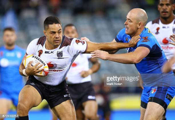 Jarryd Hayne of Fiji palms off Terry Campese of Italy during the 2017 Rugby League World Cup match between Fiji and Italy at Canberra Stadium on...