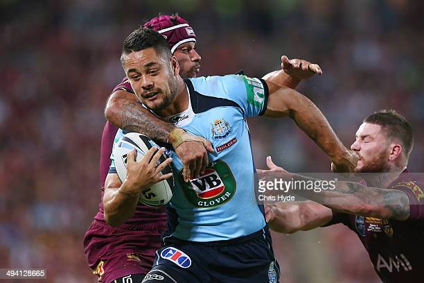 Jarryd Hayne of the Blues breaks through the defence of Johnathan Thurston and Chris McQueen of the Maroons to score a try during game one of the...