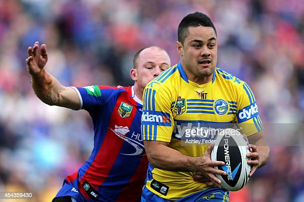 Jarryd Hayne of the Eels evades Beau Scott of the Knights during the round 25 NRL match between the Newcastle Knights and the Parramatta Eels at...