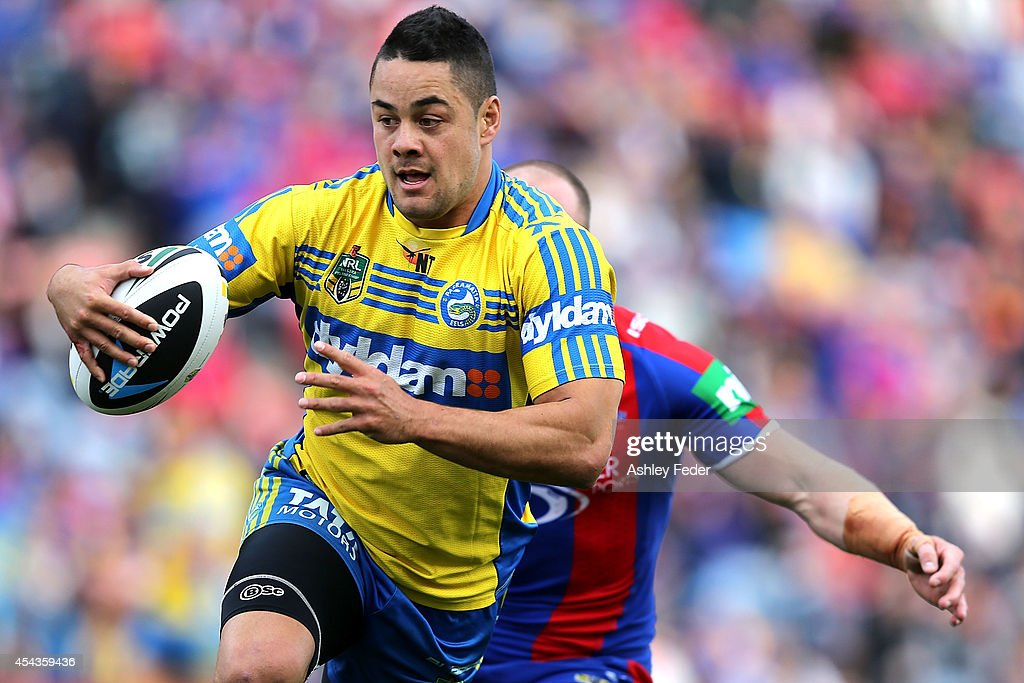 Jarryd Hayne of the Eels evades Beau Scott of the Knights during the round 25 NRL match between the Newcastle Knights and the Parramatta Eels at Hunter Stadium on August 30, 2014 in Newcastle, Australia.