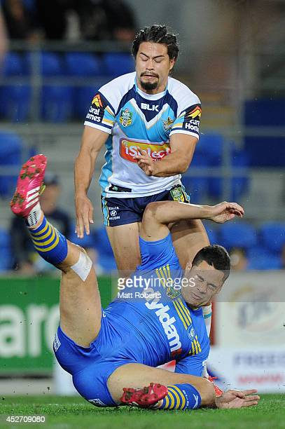 Jarryd Hayne of the Eels falls into Kevin Gordon of the Titans after a tackle attempt during the round 20 NRL match between the Gold Coast Titans and...