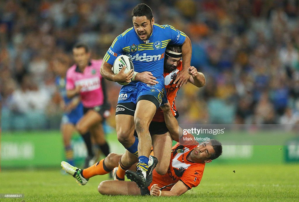 Jarryd Hayne of the Eels is tackled by Braith Anasta and Aaron Woods of the Tigers during the round seven NRL match between the Parramatta Eels and the Wests Tigers at ANZ Stadium on April 21, 2014 in Sydney, Australia.
