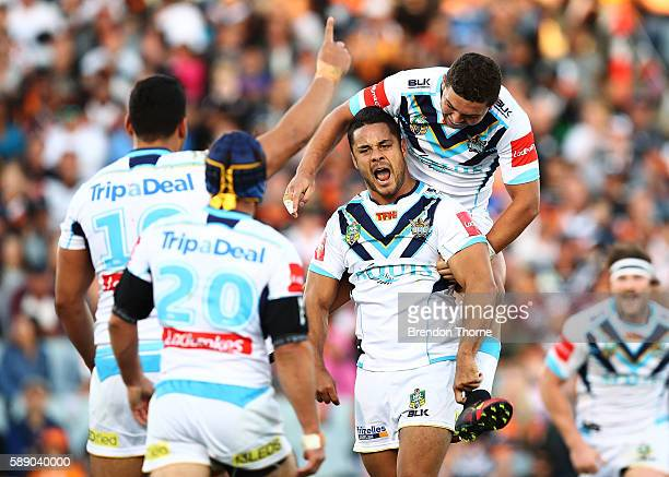 Jarryd Hayne of the Titans celebrates with team mates after kicking a drop goal to win the match during the round 23 NRL match between the Wests...