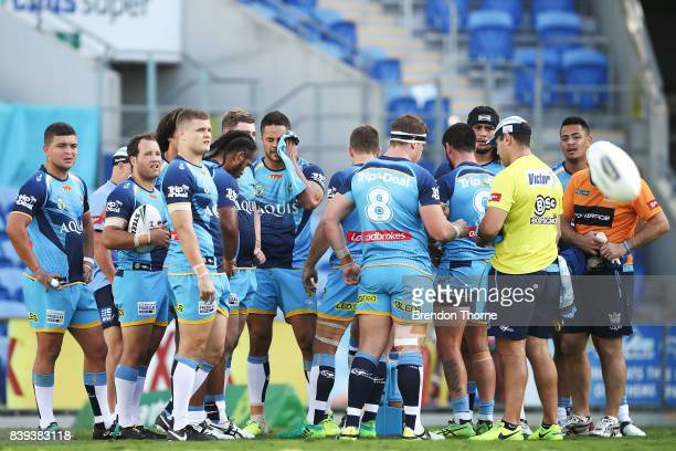 Jarryd Hayne of the Titans wipes his face as the rest of the team look on after conceding a try during the round 25 NRL match between the Gold Coast...