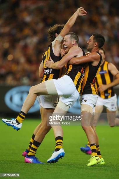 Jarryd Roughead of the Hawks celebrates a goal with Ty Vickery and Jack Gunston during the round one AFL match between the Essendon Bombers and the...