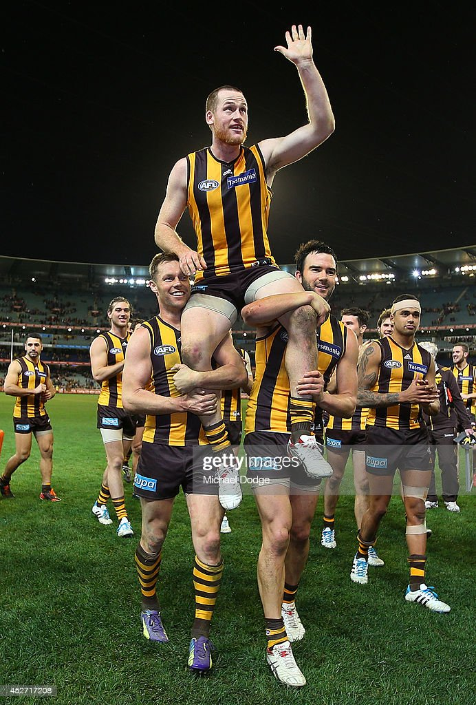 Jarryd Roughead of the Hawks gets carries off by Sam Mitchell and Jordan Lewis (R) after winning in his 200th game during the round 18 AFL match between the Hawthorn Hawks and the Sydney Swans at Melbourne Cricket Ground on July 26, 2014 in Melbourne, Australia.
