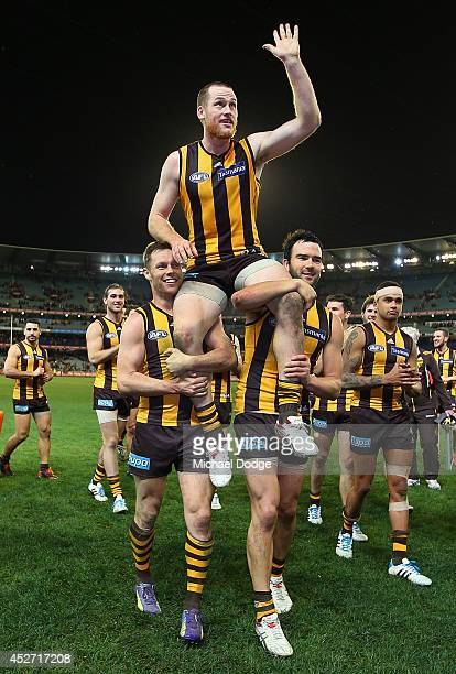 Jarryd Roughead of the Hawks gets carries off by Sam Mitchell and Jordan Lewis after winning in his 200th game during the round 18 AFL match between...