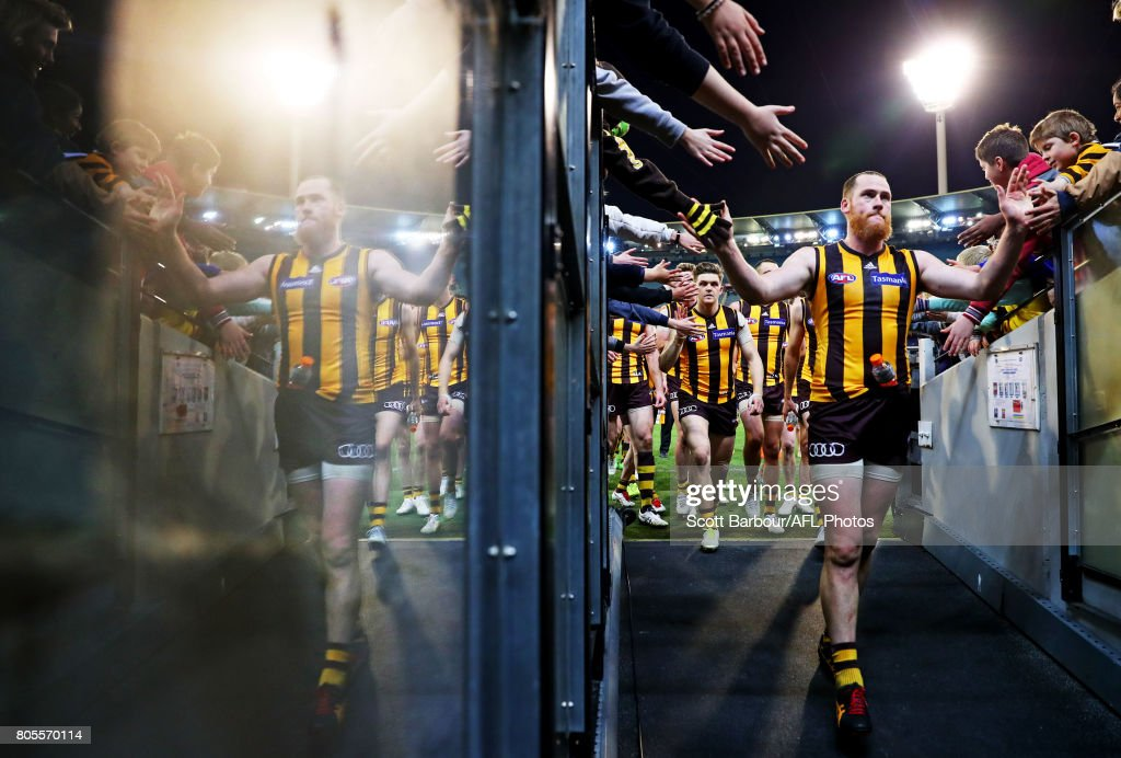 Jarryd Roughead of the Hawks is reflected in the race as he leads his team to the changing rooms and celebrates with supporters in the crowd after winning during the round 15 AFL match between the Hawthorn Hawks and the Collingwood Magpies at Melbourne Cricket Ground on July 2, 2017 in Melbourne, Australia.
