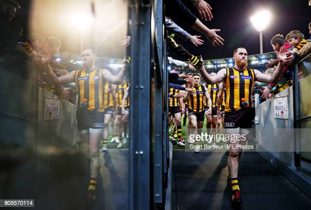 Jarryd Roughead of the Hawks is reflected in the race as he leads his team to the changing rooms and celebrates with supporters in the crowd after...