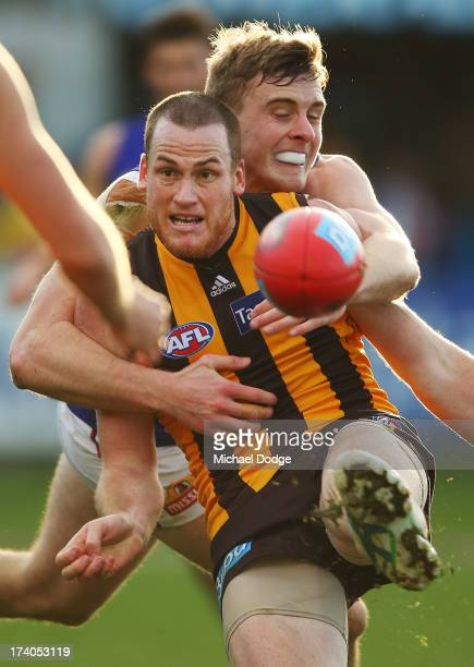 Jarryd Roughead of the Hawks kicks the ball against Jordan Roughead of the Bulldogs during the round 17 AFL match between the Hawthorn Hawks and the...