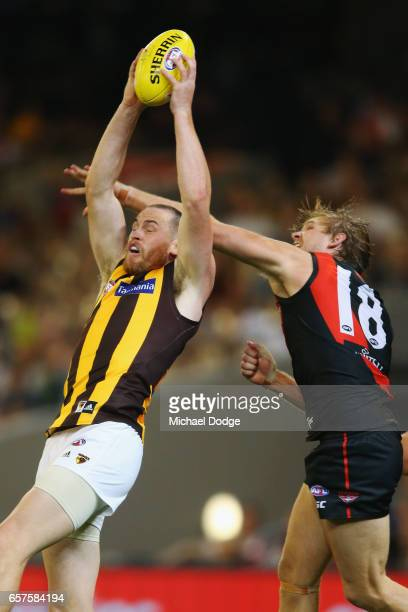 Jarryd Roughead of the Hawks marks the ball against Michael Hurley of the Bombers during the round one AFL match between the Essendon Bombers and the...