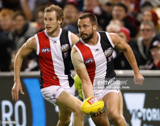 Jarryn Geary of the Saints handpasses the ball ahead of Jimmy Webster of the Saints during the 2017 AFL round 13 match between the North Melbourne...