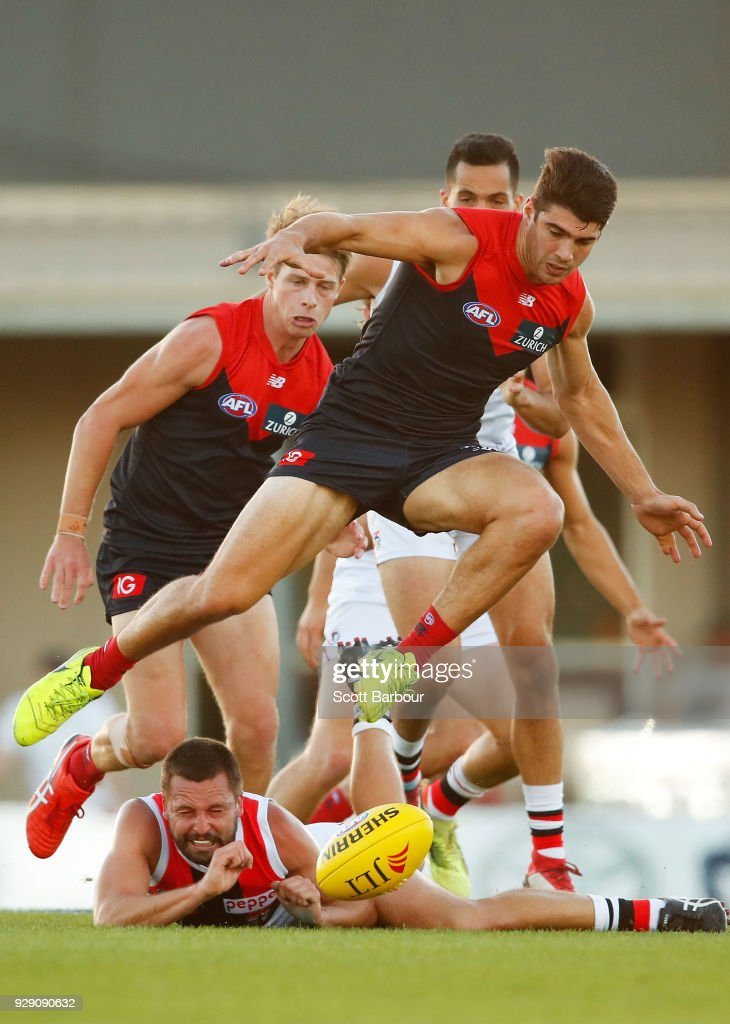 Jarryn Geary of the Saints is tackled as Christian Petracca of the Demons jumps over him during the JLT Community Series AFL match between the Melbourne Demons and the St Kilda Saints at Casey Fields on March 8, 2018 in Melbourne, Australia.