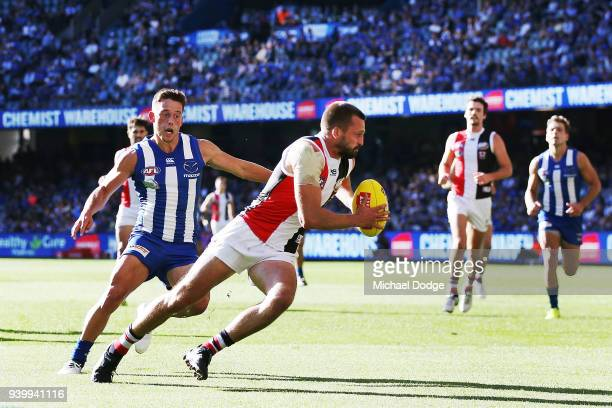 Jarryn Geary of the Saints runs with the ball from Nathan Hrovat of the Kangaroos during the round two AFL match between the North Melbourne...