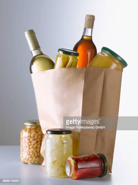 jars and bottles in a brown paper bag - 布の袋 ストックフォトと画像