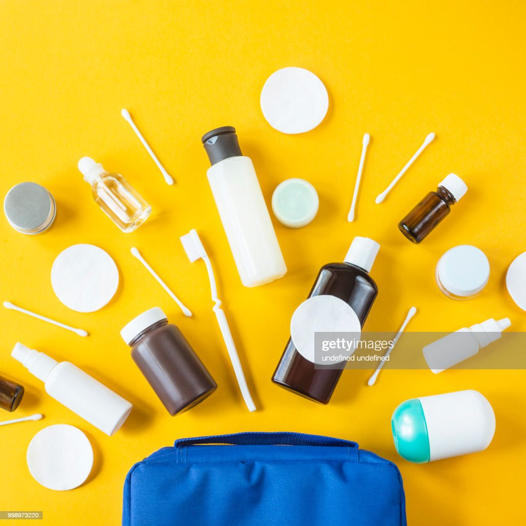 Jars and containers with cosmetics and cotton buds with disks from a blue cosmetic bag on a yellow background. Top view, flat lay : Stock Photo