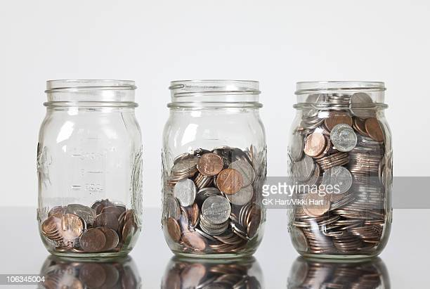 jars of coins - jar stock pictures, royalty-free photos & images