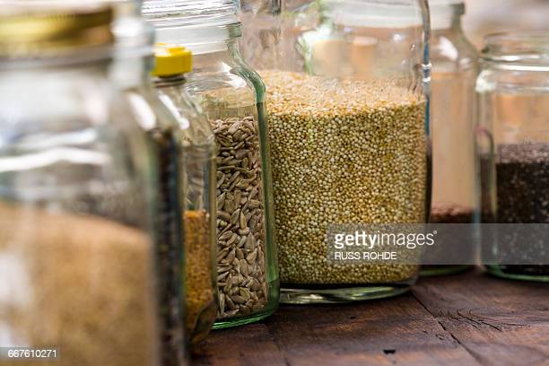 Jars of quinoa, sunflower, linseed on table