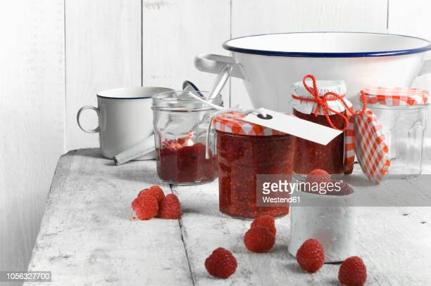 Jars of raspberry jam and raspberries