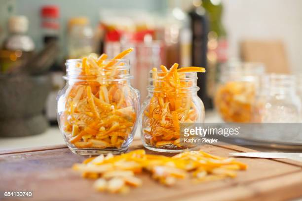 Jars on kitchen counter filled with thinly cut orange zest