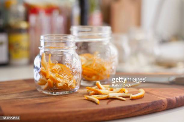Jars on wooden cutting board filled with thinly cut orange zest