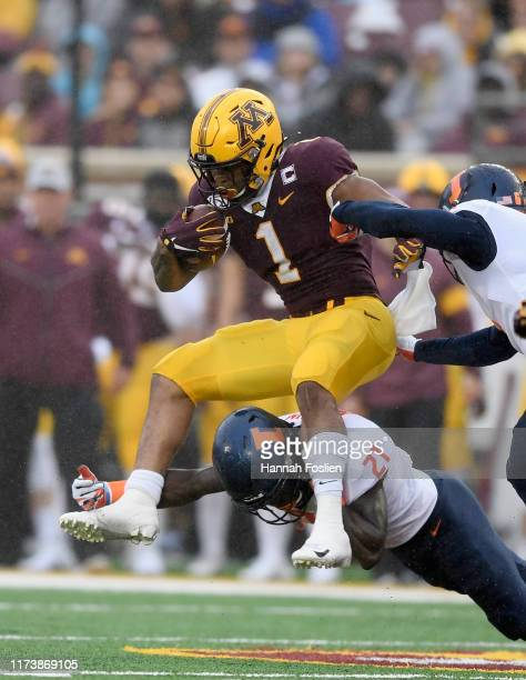 Jartavius Martin and Tony Adams of the Illinois Fighting Illini tackle Rodney Smith of the Minnesota Gophers during the second quarter of the game at...