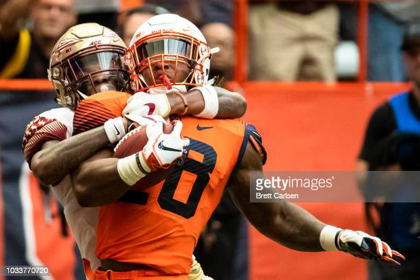 Jarveon Howard of the Syracuse Orange is brought down by Cyrus Fagan of the Florida State Seminoles after a first down run during the second half at...
