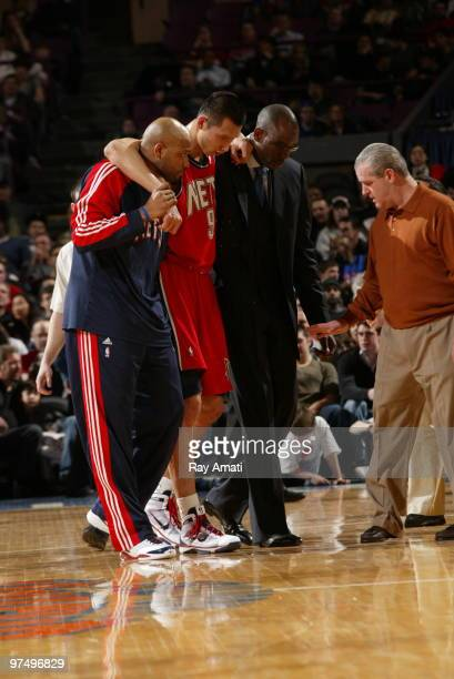 Jarvis Hayes and Assistant Coach Roy Rogers and Head Athletic Trainer Tim Walsh helps Yi Jianlian of the New Jersey Nets off the court as he is...