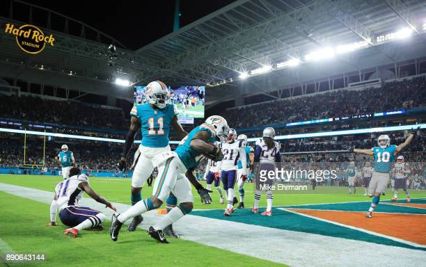 Jarvis Landry celebrates with DeVante Parker of the Miami Dolphins after scoring a touchdown in the second quarter against the defense of Jonathan...
