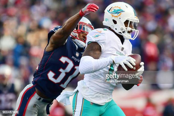 Jarvis Landry of the Miami Dolphins carries the ball as he is tackled by Jonathan Jones of the New England Patriots during the second quarter of a...