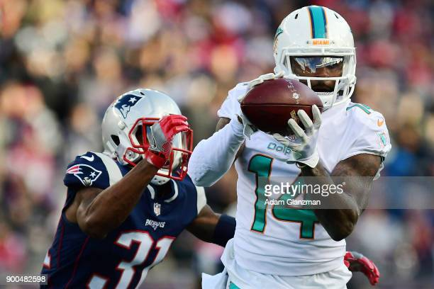 Jarvis Landry of the Miami Dolphins coaches the ball while under pressure from Jonathan Jones of the New England Patriots during a game at Gillette...