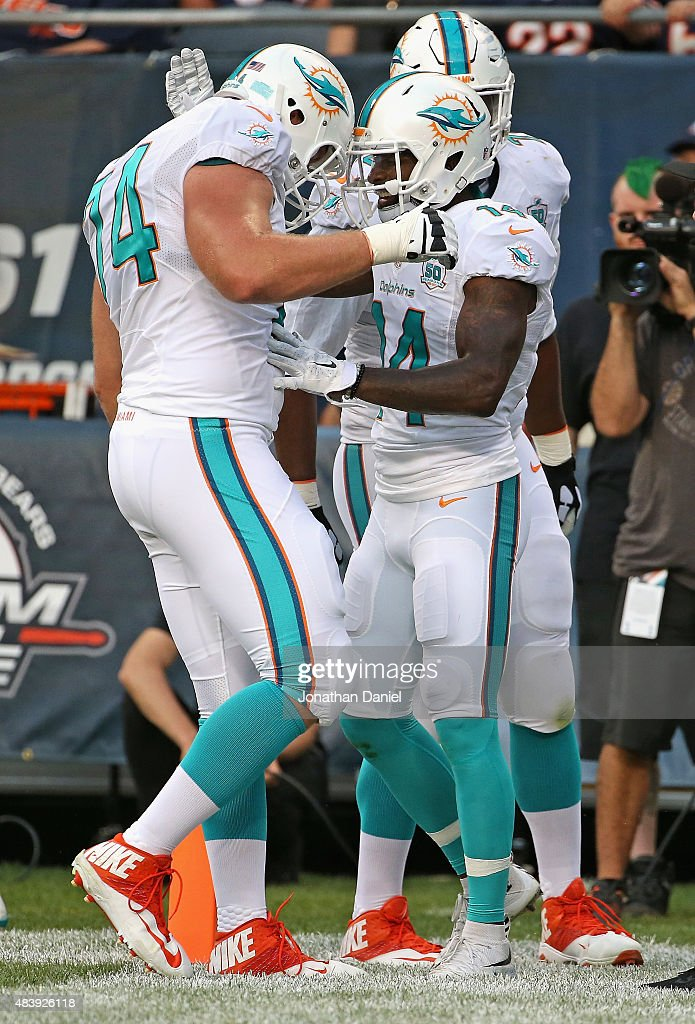 Jarvis Landry #14 of the Miami Dolphins is congratulated by Jason Fox #74 after scoring a touchdown against the Chicago Bears during a preseason game at Soldier Field on August 13, 2015 in Chicago, Illinois.