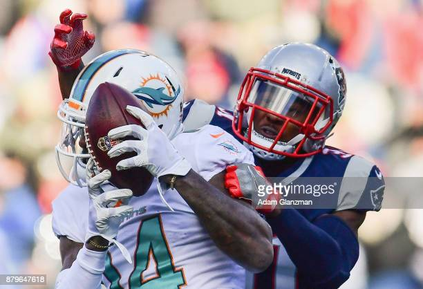 Jarvis Landry of the Miami Dolphins is defended by Jonathan Jones of the New England Patriots during the second quarter of a game at Gillette Stadium...