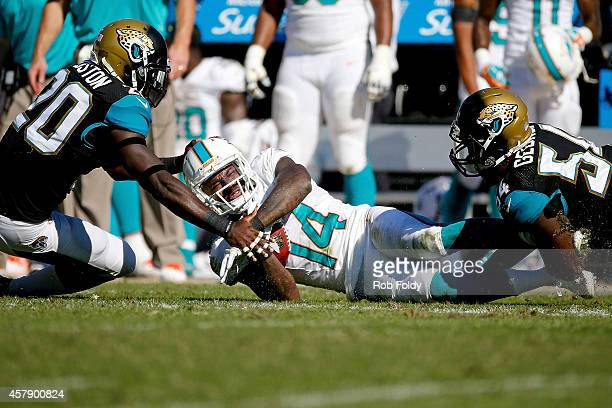 Jarvis Landry of the Miami Dolphins is stopped by Paul Posluszny and Craig Loston of the Jacksonville Jaguars during the third quarter of the game at...