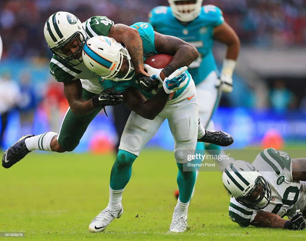 Jarvis Landry #14 of the Miami Dolphins is tackled by Buster Skrine #41 of the New York Jets during the game at Wembley Stadium on October 4, 2015 in London, England.
