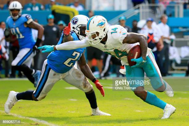 Jarvis Landry of the Miami Dolphins tries to avoid the tackle of Da'Norris Searcy of the Tennessee Titans in the fourth quarter on October 8 2017 at...