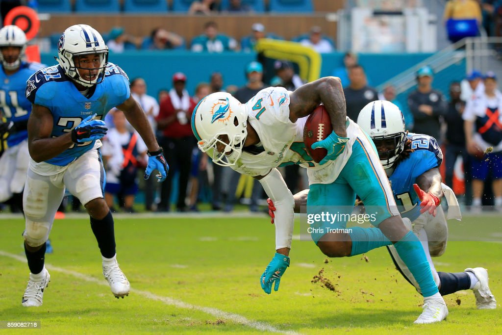 Jarvis Landry #14 of the Miami Dolphins tries to avoid the tackle of Da'Norris Searcy #21 of the Tennessee Titans in the fourth quarter on October 8, 2017 at Hard Rock Stadium in Miami Gardens, Florida.