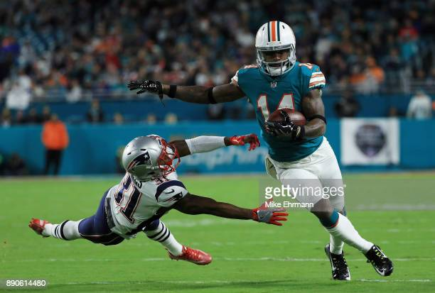 Jarvis Landry of the Miami Dolphins tries to avoid the tackle of Jonathan Jones of the New England Patriots in the first quarter at Hard Rock Stadium...
