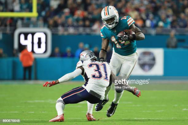 Jarvis Landry of the Miami Dolphins tries to avoid the tackle of Jonathan Jones of the New England Patriots in the third quarter at Hard Rock Stadium...