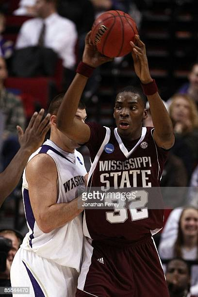 Jarvis Varnado of the Mississippi State Bulldogs looks to pass the ball as he is covered by Jon Brockman during the first round of the NCAA Division...