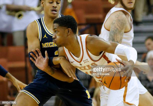 Jase Febres of the Texas Longhorns drives around Jordan Poole of the Michigan Wolverines at the Frank Erwin Center on December 12 2017 in Austin Texas