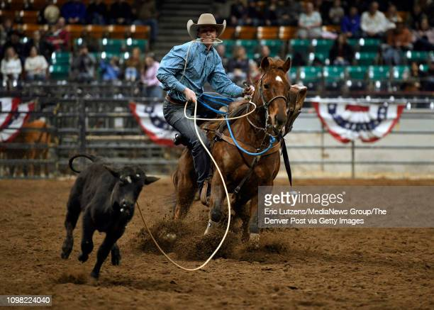 Jase Staudt of Northrop Colorado dismounts his horse while competing in the TX Whiskey Tie Down Roping competition during the Pro Rodeo Military...
