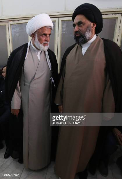 Jasim alJazaeri member of the Iraqi Hezbollah Brigades part of the Hashed alShaabi paramilitary units speaks to a Shiite cleric during a ceremony in...